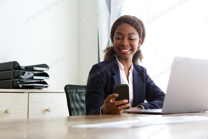 professional woman sitting in office and looking at cell phone