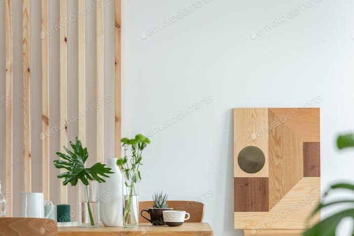 Grüne Pflanzen in kleinen Vasen auf langen Holz-Esstisch in hellen Innenraum