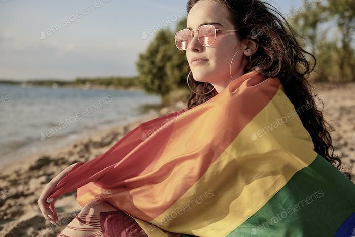 Young woman wrapped in rainbow flag on the beach