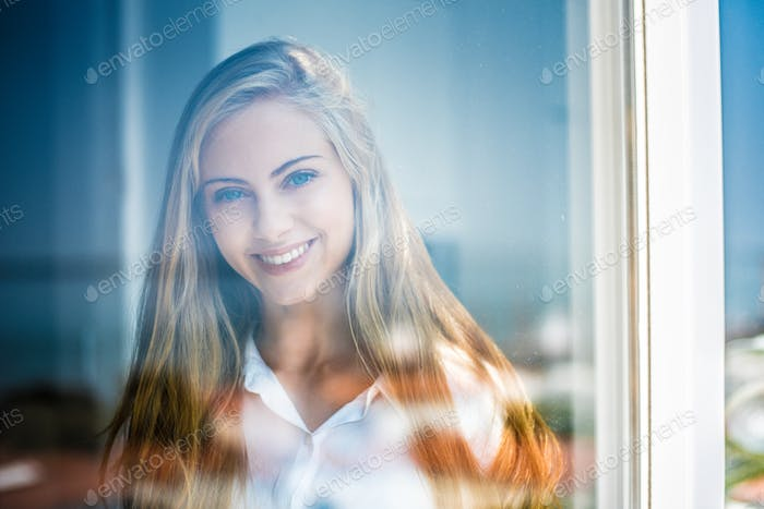 Junge nachdenkliche Frau Blick durch das Fenster