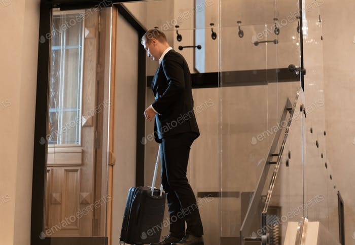 Businessman with suitcase standing near hotel doorway