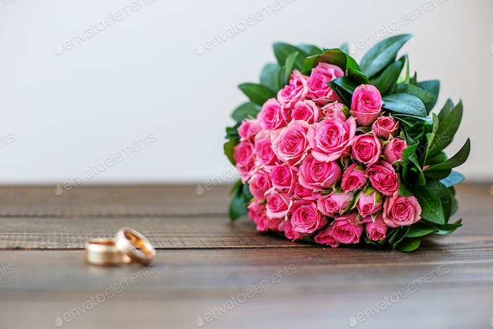 Wedding bouquet of pink roses. Wedding ring. Copy space. The con