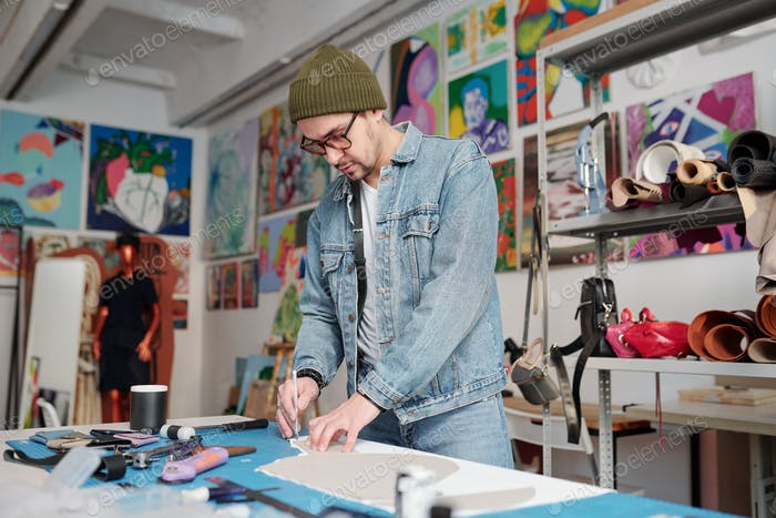 Handicraft master in beanie hat, denim jacket and jeans working by table