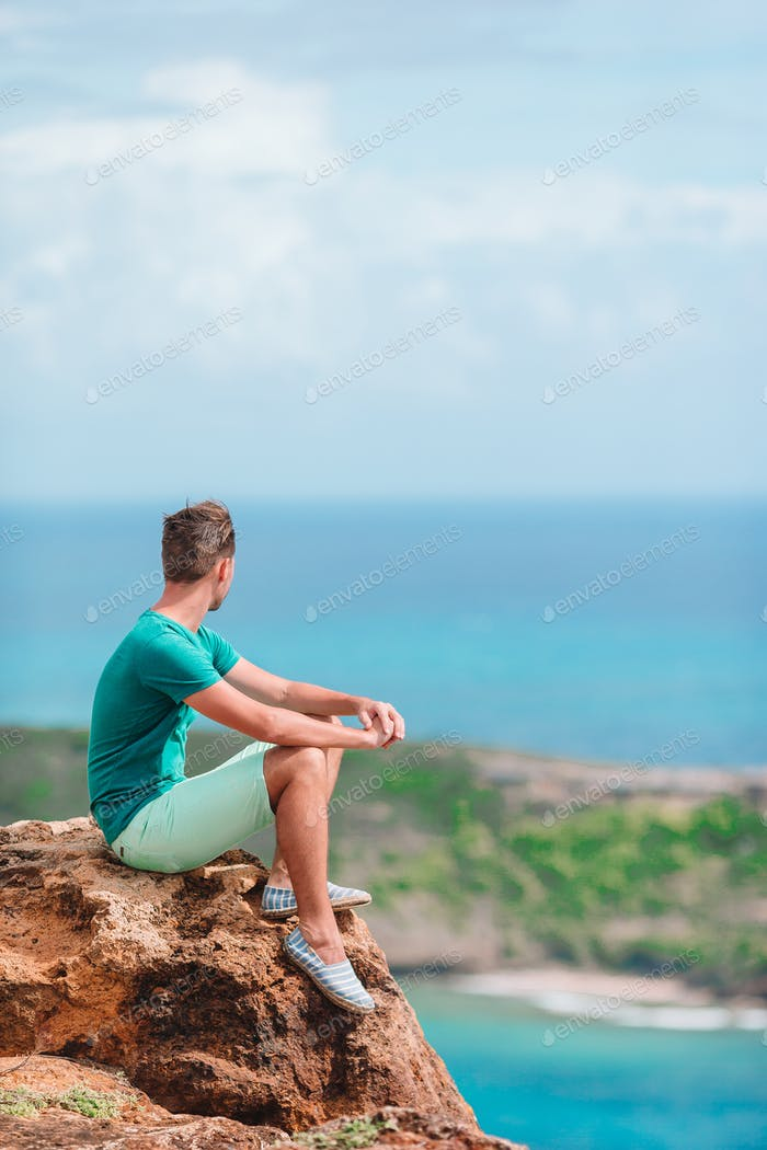 Young man enjoying breathtaking views of beautiful landscape