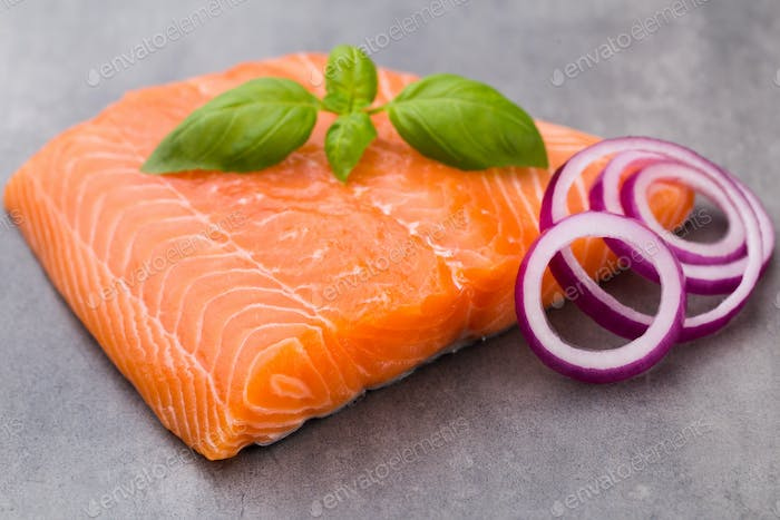 Fresh salmon fille with spice on the grey background.