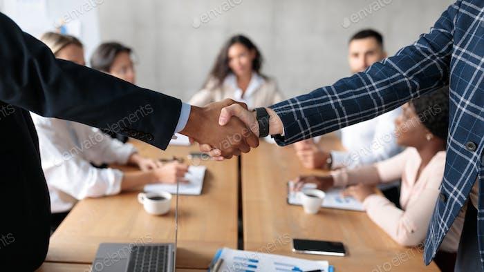 Handshake bei Geschäftstreffen, zwei Geschäftsleute beim Händeschütteln im Büro