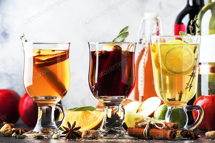 Mulled wine and cider. Hot winter drinks and cocktails in glass mugs with spices and citrus fruit