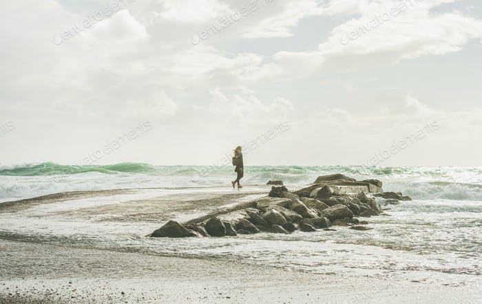 Young woman standing on pier and enjoying stormy sea