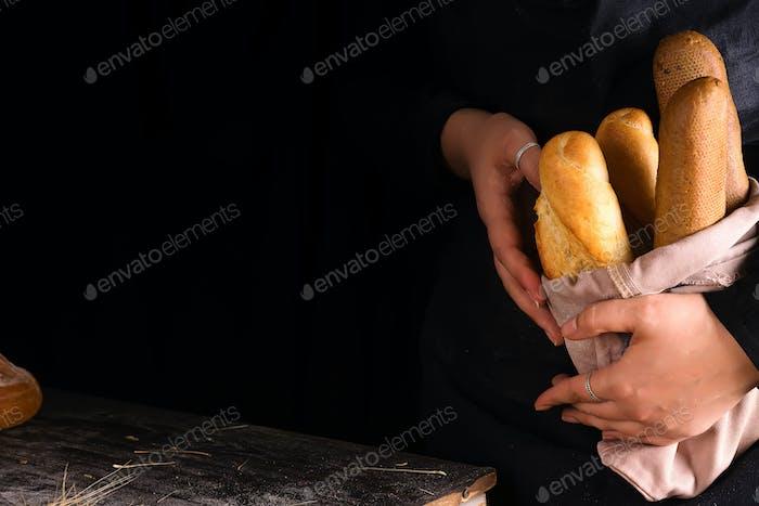 Woman holding tasty fresh bread sorts on a dark