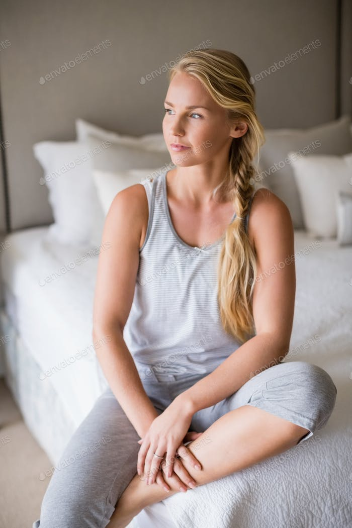 Thoughtful beautiful woman sitting on bed in bedroom