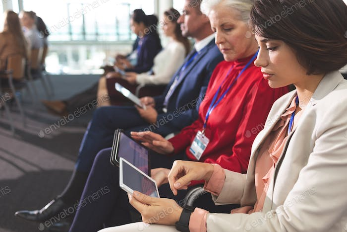 Business people using digital tablet during business seminar in office building