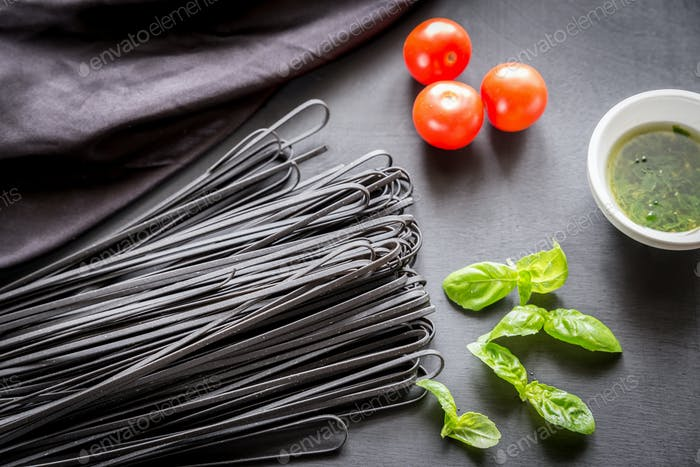 Raw black pasta with basil and tomatoes