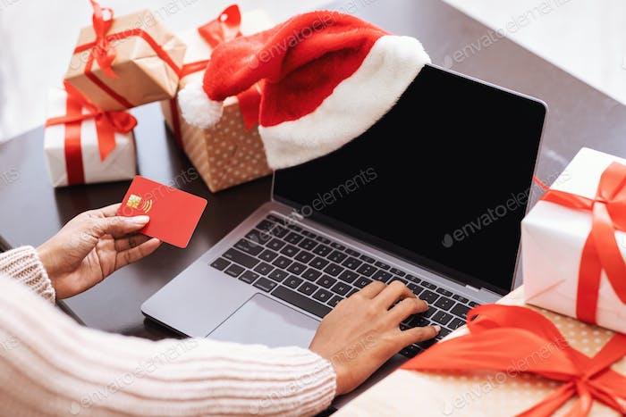 Weihnachtseinkauf. Schwarze Dame mit Laptop und Kreditkarte