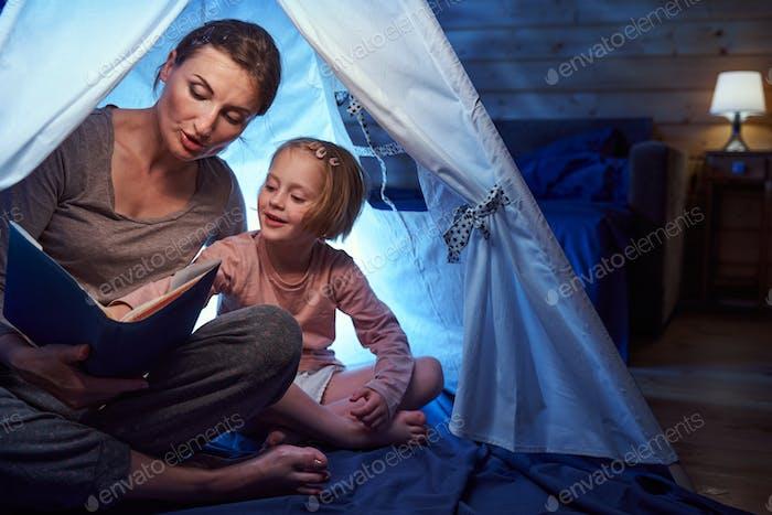 Interessiertes Mädchen zeigt auf Märchenbuch in einem Zelt auf dem Bett