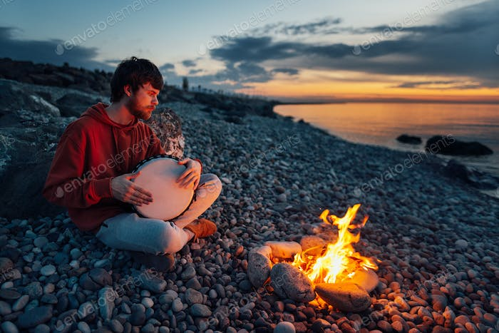 percussionist guy plays a djembe sitting on beach by the fire at