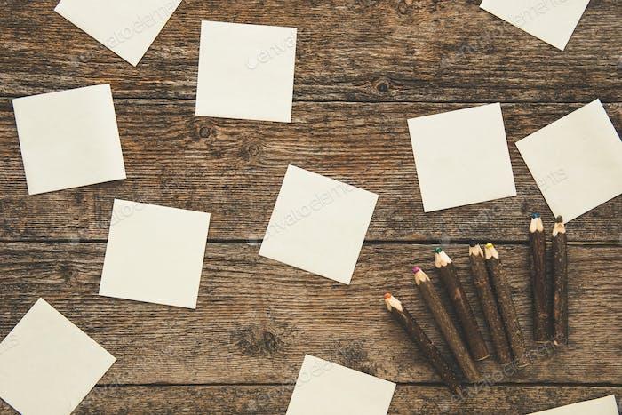Weiße Haftnotizen und Set von Buntstiften auf Holzhintergrund