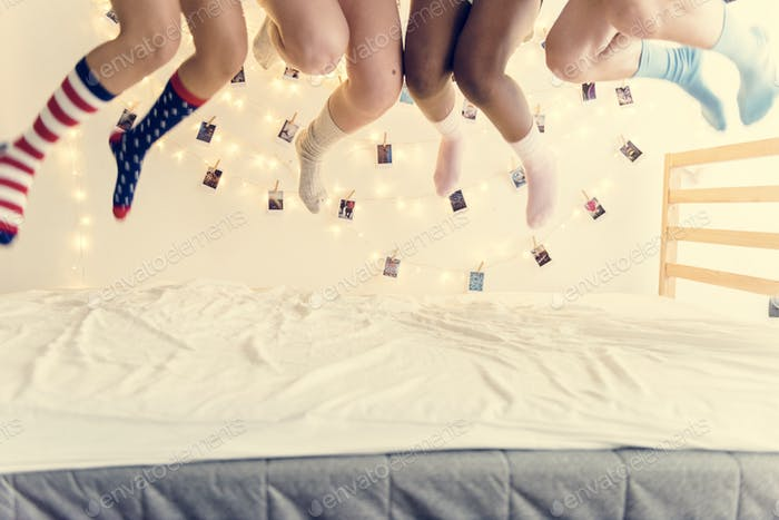 Closeup of two pairs of legs with socks jumping on the bed
