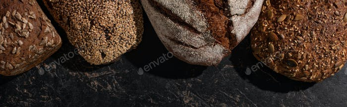Top View of Fresh Baked Whole Grain Bread on Stone Black Surface, Panoramic Shot