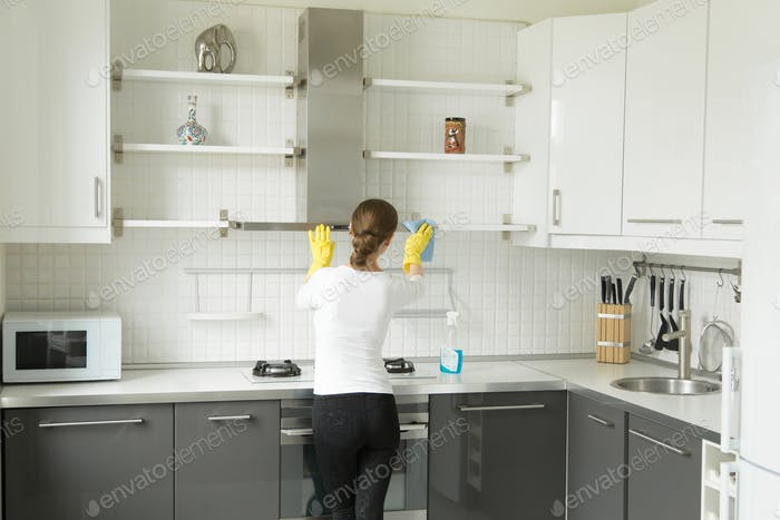 Rear view at a young woman washing kitchen closet