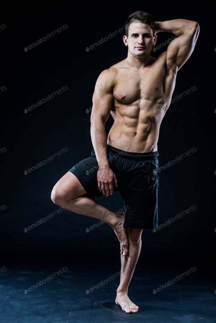 Young strong athlete is making yoga on black background
