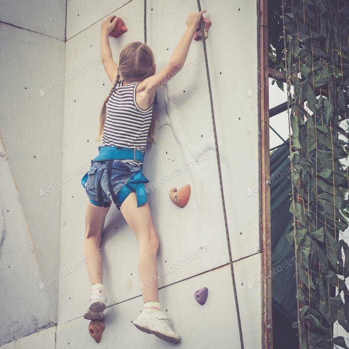 little girl climbing a rock wall outdoor.