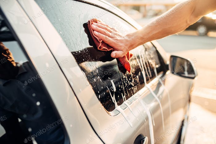 Male hand rubbing car window with foam, carwash