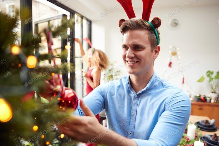 Mann trägt Fancy Dress Geweih als Paar zu Hause Hängende Dekorationen auf Weihnachtsbaum zusammen