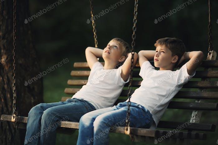 kleine Jungen Reiten auf einer Schaukel
