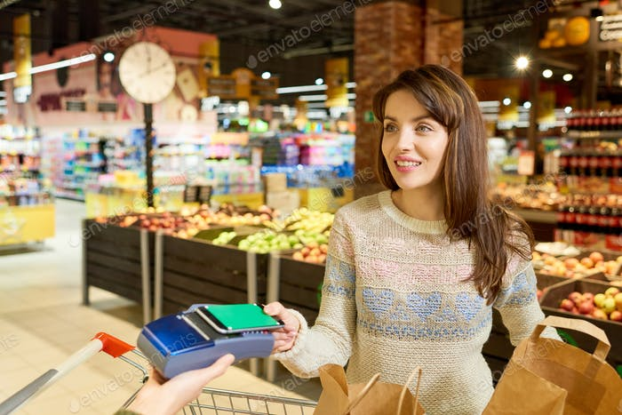 Woman Paying via Smartphone in Grocery Store