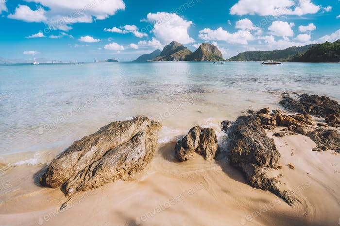 Sandy Beach with rocks and mountains in Background, El Nido, Palawan, Philippines