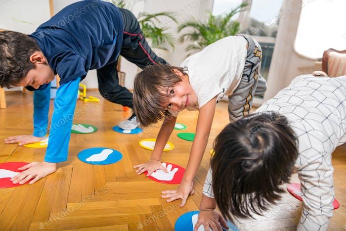 Gruppe von Kindern, die Twister Drinnen spielen