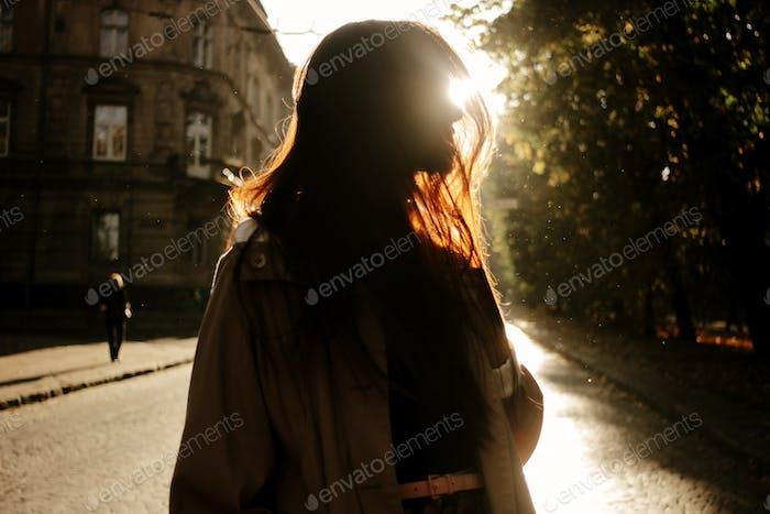 happy stylish woman having fun in sunny city street