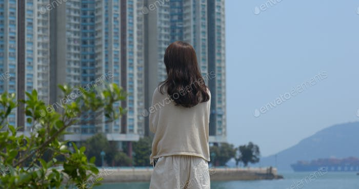 Woman enjoy the view of the sea with the background of building