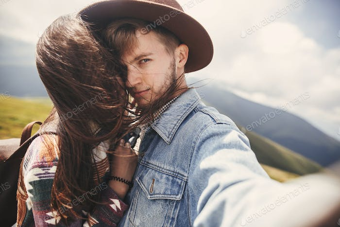 Happy hipster couple making selfie on top of windy mountains