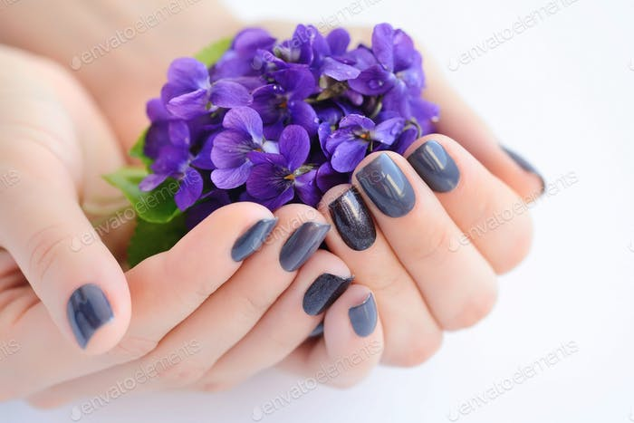 Hands of a woman with dark manicure on nails and flowers violets