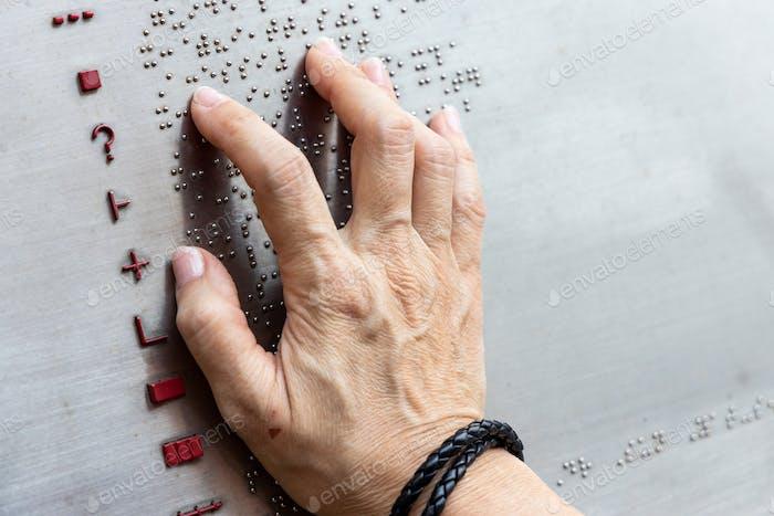 Finger reading braille tactile on public park message board