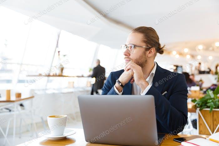 Konzentrierte junge Geschäftsmann mit Laptop-Computer.