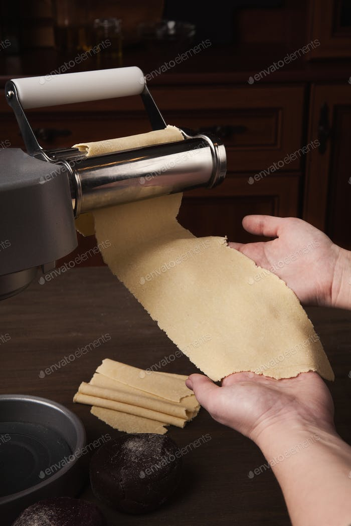 Rolling raw dough with pasta machine