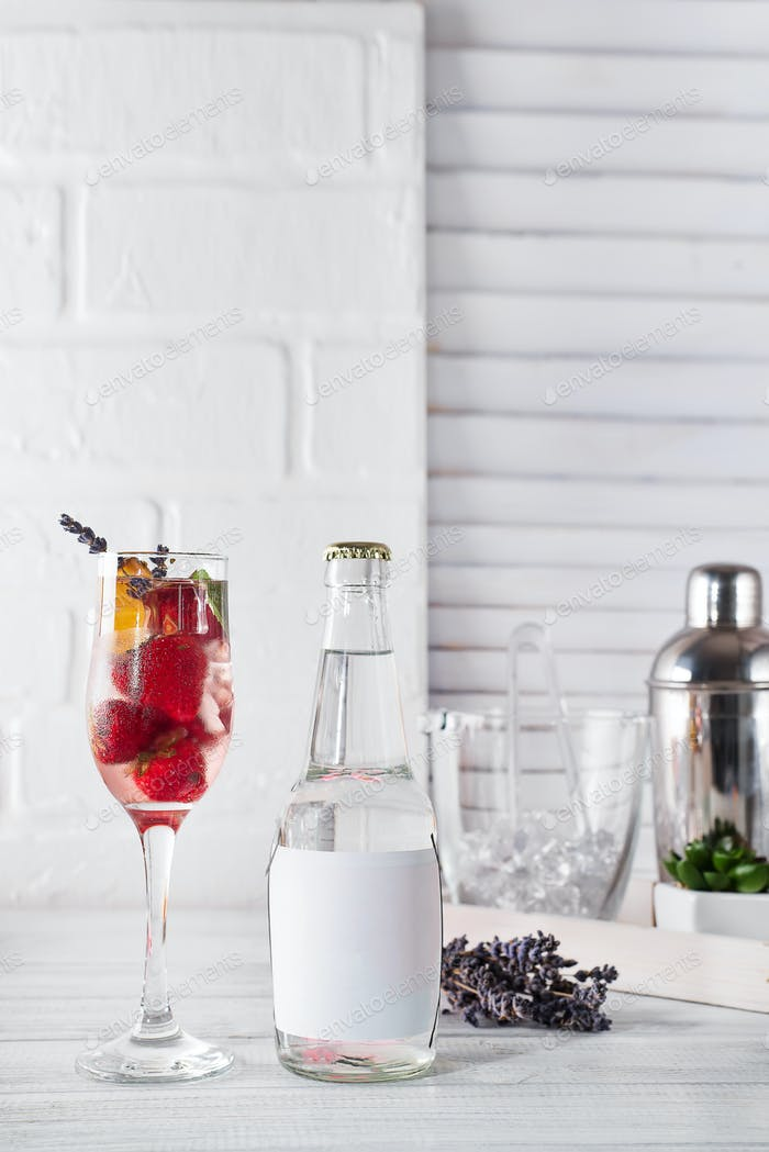 Red Cocktail with ice and strawberry, ginger and lavender with a bottle of tonic and a place under