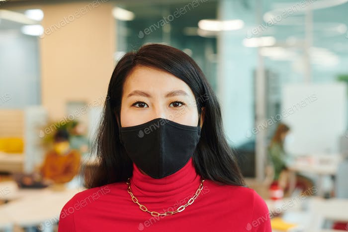Young pretty female manager of Asian ethnicity standing in open space office