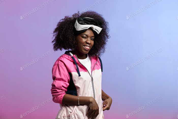 Funny curly brown-haired girl dressed in the pink sports jacket wears on her head the virtual