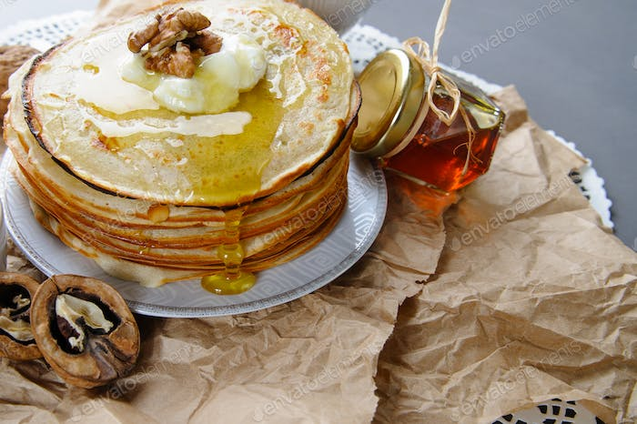 Stack of pancakes on a paper napkin, served with honey and walnu