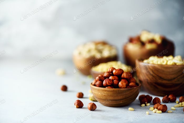 Hazelnuts in wooden bowl. Food mix background, top view, copy space, banner. Assortment of nuts -