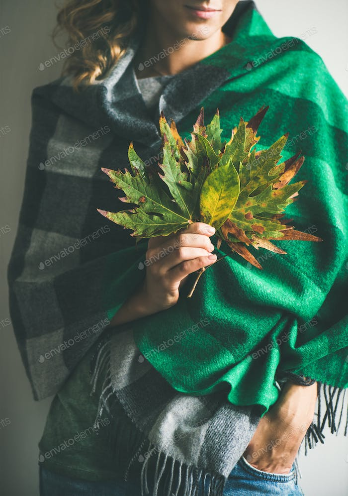 Woman in scarf or blanket and jeans with Autumn leaves