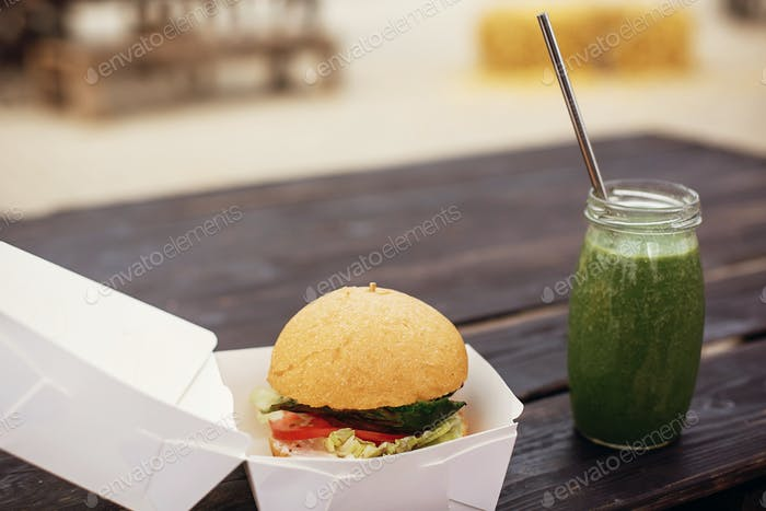 Vegan burger and healthy spinach smoothie in glass jar with metal reusable straw