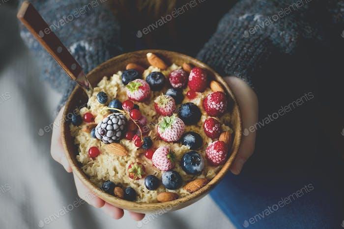 Woman hands holding oatmeal porridge with frozen berries, almonds in wooden bowl. Banner. Healthy