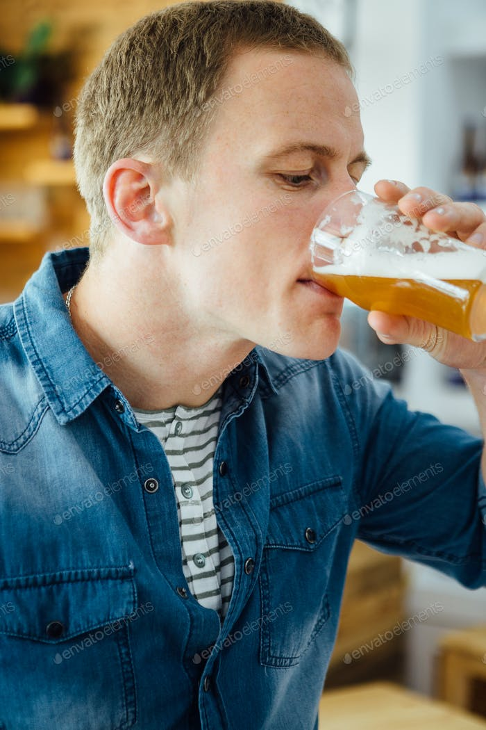 Handsome young man drinking light beer