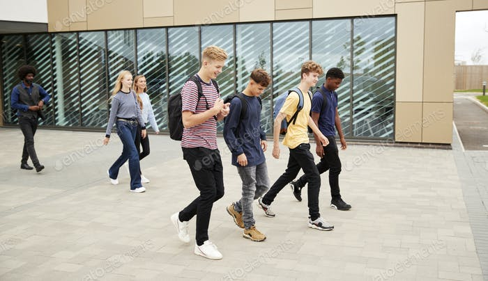 Group Of High School Students Walking Out Of College Building Together