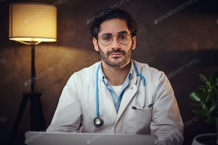 Junger Arzt in Brille in seinem Büro