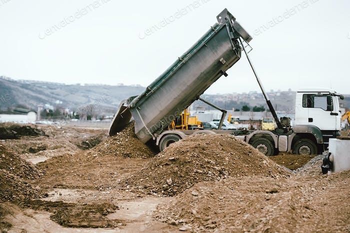 Industrial heavy duty dumper truck unloading gravel for leveling